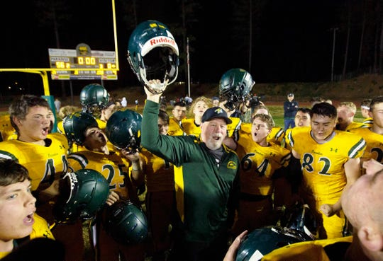 In this Nov. 15, 2019, file photo, Paradise High School head football coach Rick Prinz, center, celebrates with his team after defeating Live Oak High School  in their Northern California Division III playoff game in Paradise, Calif.  The  Northern California high school football team is preparing to play for a championship one year after most of the players and coaches lost their homes to a wildfire that nearly destroyed their town. Paradise High School will face Sutter Union High School on Saturday night, Nov. 30, for the Northern Section Division III championship.