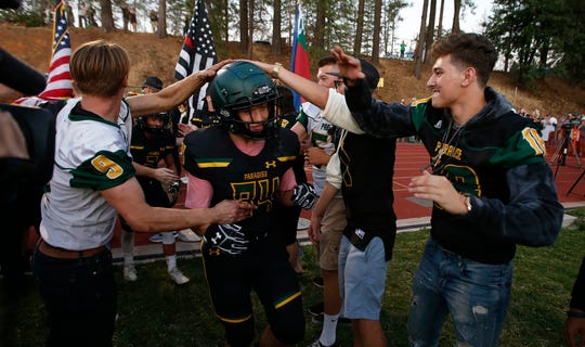 In this Aug. 23, 2019, file photo, Paradise tight end Jacob Duncan runs through a tunnel of former players during the opening ceremony of their high school football game against Williams, in Paradise, Calif.  The  Northern California high school football team is preparing to play for a championship one year after most of the players and coaches lost their homes to a wildfire that nearly destroyed their town. Paradise High School will face Sutter Union High School on Saturday night, Nov. 30  for the Northern Section Division III championship.