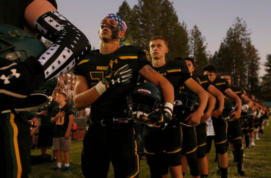 In this Aug. 23, 2019, file photo, members of the Paradise High School football team stand for the playing of the national anthem before their game against Williams High School in Paradise, Calif. The  Northern California high school football team is preparing to play for a championship one year after most of the players and coaches lost their homes to a wildfire that nearly destroyed their town. Paradise High School will face Sutter Union High School on Saturday night, Nov. 30, for the Northern Section Division III championship.