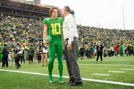 Nov 30, 2019; Eugene, OR, USA; Oregon Ducks quarterback Justin Herbert (10) listens to head coach Mario Cristobal during senior day introductions before a game against the Oregon State Beavers at Autzen Stadium. Mandatory Credit: Troy Wayrynen-USA TODAY Sports