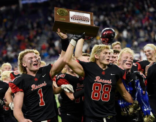 Jack Steil and Andrew Anderson hoist the state championship trophy after an overtime win in the Class 4A state championship game over SMB, Friday, Nov. 29, 2019, at U.S. Bank Stadium.