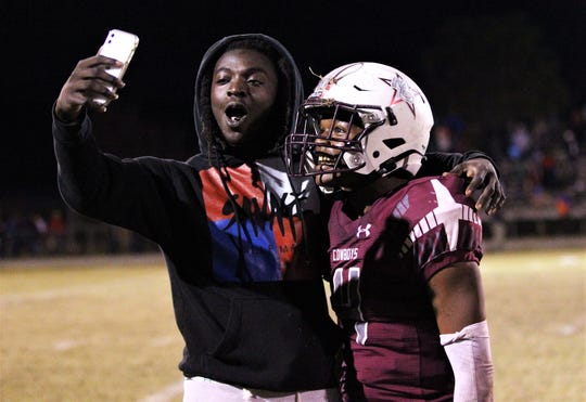 Madison County senior quarterback Vinsonta Allen takes a selfie with Travis Jay as the Cowboys beat Pahokee 37-36 in a Class 1A state semifinal at Boot Hill Stadium on Nov. 29, 2019.