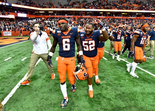 Syracuse defensive back Trill Williams (6) is congratulated by defensive lineman Curtis Harper (52) after his fumble return for a touchdown sealed the win against Wake Forest in an NCAA college football game in Syracuse, N.Y., Saturday, Nov. 30, 2019. Syracuse beat Wake Forest 39-30 in overtime. (AP Photo/Adrian Kraus)