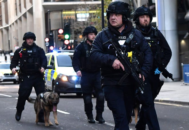 Armed police with dogs patrol along Cannon Street in central London, on Nov. 29, 2019.