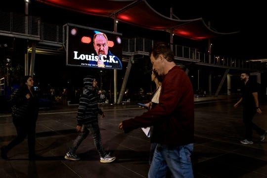 Israelis walk past a billboard showing comedian Louis C.K. in the Israeli city of Holon near Tel Aviv.