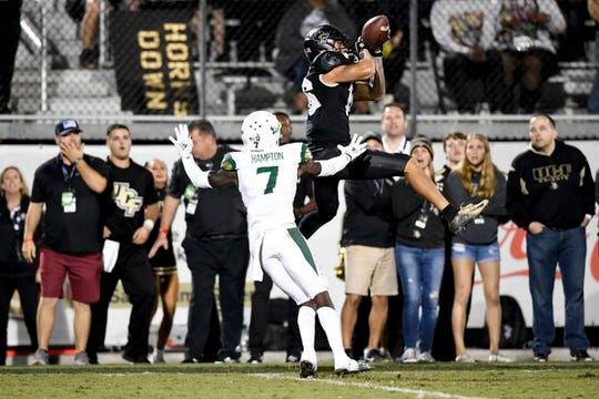 University of Central Florida Knights wide receiver Tre Nixon (16) of Viera makes a reception in front of South Florida Bulls defensive back Mike Hampton (7) during the second half at Spectrum Stadium.