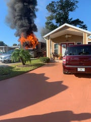 Firefighters extinguished a recreational vehicle fire that threatened to spread to a nearby home