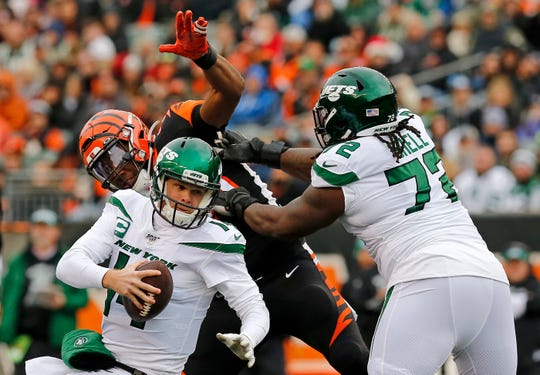 New York Jets quarterback Sam Darnold (14) is knocked to the ground by Cincinnati Bengals defensive end Carlos Dunlap (96) in the first quarter of the NFL Week 13 game between the Cincinnati Bengals and the New York Jets at Paul Brown Stadium in downtown Cincinnati on Sunday, Dec. 1, 2019. The Bengals led 17-6 at halftime.