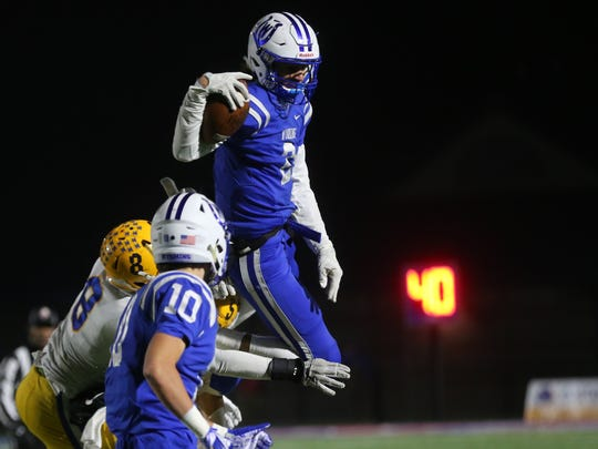 Wyoming quarterback Evan Prater (2) jumps over a Clyde defender during their state semifinal football game Saturday, Nov. 30, 2019.