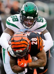 Cincinnati Bengals running back Joe Mixon (28) is brought down on a carry by New York Jets outside linebacker James Burgess (58) in the second quarter of the NFL Week 13 game between the Cincinnati Bengals and the New York Jets at Paul Brown Stadium in downtown Cincinnati on Sunday, Dec. 1, 2019. The Bengals led 17-6 at halftime.