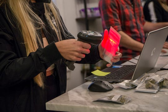 Arbors Wellness rings up its first sale to the general public on Michigan's first day of legal marijuana in Ann Arbor, Mich., Sunday, Dec. 1, 2019.