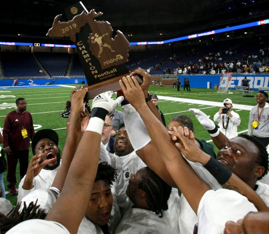 River Rouge celebrates with their first state championship trophy after winning the Division 3 state championship football game 30-7 against Muskegon at Ford Field on Saturday, Nov. 30, 2019.