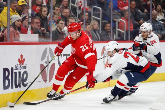 Detroit Red Wings defenseman Dennis Cholowski battles for the puck with Washington Capitals left wing Brendan Leipsic during the first period at Little Caesars Arena, Nov. 30, 2019.