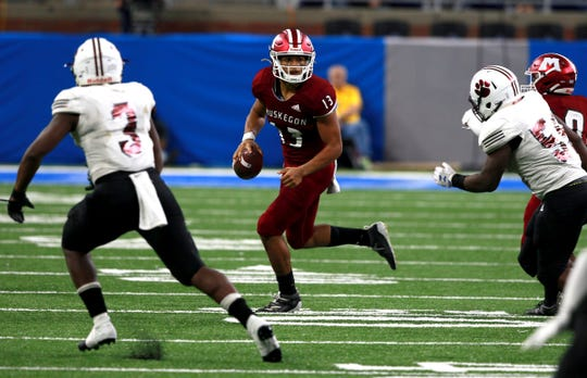 Muskegon quarterback #13 Camron Martinez scrambles out of the pocket as the defense of River Rouge closes in during the third quarter of the Division 3 state championship football game against Muskegon at Ford Field on Saturday, Nov. 30, 2019. River Rouge won the game 30-7 to win their first ever state football championship.