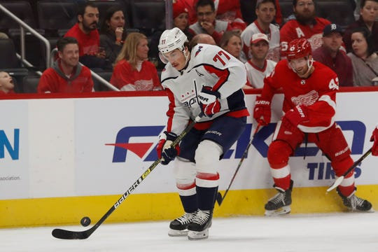 Washington Capitals right wing T.J. Oshie controls the puck ahead of Detroit Red Wings center Darren Helm during the first period Saturday, Nov. 30, 2019, in Detroit.