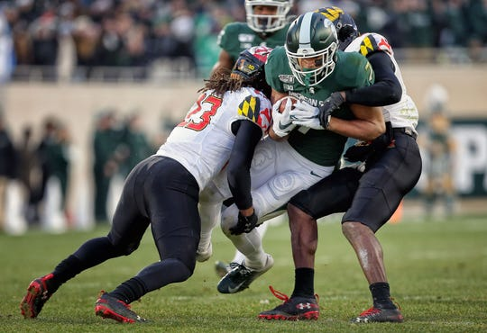 Cody White is tackled by Maryland's Fa'Najae Gotay (23) at Spartan Stadium.