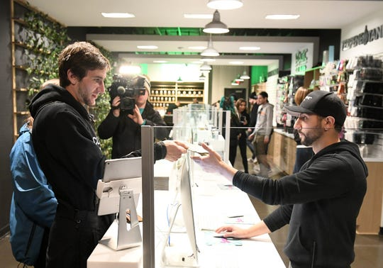 Kelly Savage, 25, of Ohio, left, makes the first purchase of recreational marijuana giving cash to general manager Nick Warra, right, at Exclusive Provisioning Center in Ann Arbor, Mich. on Dec. 1, 2019.