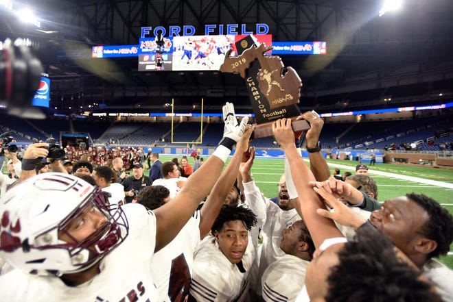 The River Rouge football team hoists the Division 3 trophy after defeating Muskegon 30-17 to win the state title in 2019.