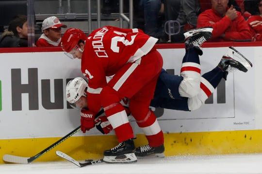 Detroit Red Wings defenseman Dennis Cholowski (21) checks Washington Capitals center Lars Eller (20).