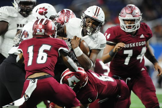 River Rouge quarterback Mareyohn Hrabowski tries to squeeze out of trouble against Muskegon.