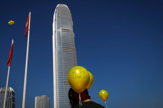 """A man stands near the balloons during a """"No Tear Gas"""" rally in Hong Kong, Sunday, Dec. 1, 2019."""