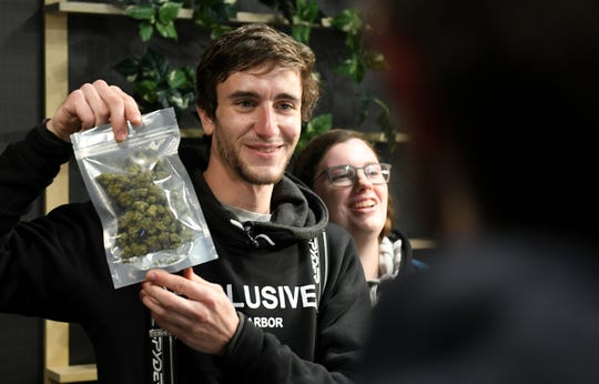 Kelly Savage, 25, of Ohio, left, with Karessa Elsberry, right, makes the first purchase of recreational marijuana at Exclusive Provisioning Center in Ann Arbor on Dec. 1, 2019.