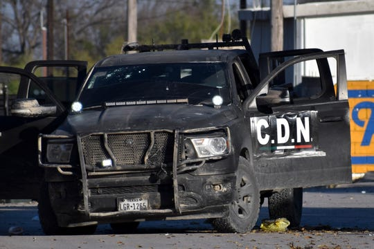 A damaged pickup marked with the initials C.D.N., that in Spanish stand for Cartel of the Northeast, is on the streets after a gun battle between Mexican security forces and suspected cartel gunmen, in Villa Union, Mexico, Saturday, Nov. 30, 2019.