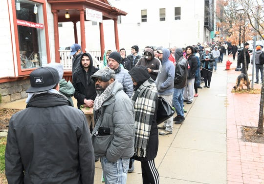 A long line stretches along a block from Arbors Wellness in Ann Arbor on Dec. 1, the first day of legal recreational marijuana sales in Michigan.