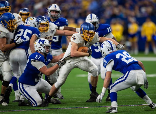 East Noble Knights' Bailey Parker (1) is taken down by Memorial's defense at the Evansville Memorial vs East Noble IHSAA Class 4A State Championship game at Lucas Oil Stadium in Indianapolis, Ind., Saturday, Nov. 30, 2019.  Memorial won the state title in a 21-3 victory over East Noble.