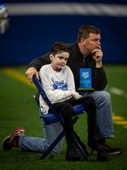 Sam Schulz, 15, left, sits with his father Patrick Schulz on the sidelines of the Evansville Memorial vs East Noble IHSAA Class 4A State Championship game at Lucas Oil Stadium in Indianapolis, Ind., Saturday, Nov. 30, 2019.  Memorial won the state title in a 21-3 victory over East Noble.