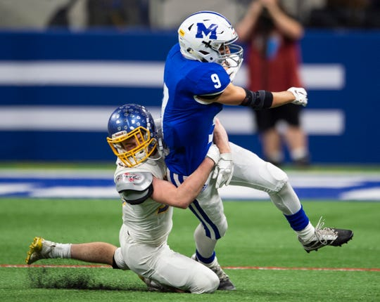 East Noble Knights' Jacob VanGorder (34) takes down Memorial's Josh Russell (9) the Evansville Memorial vs East Noble IHSAA Class 4A State Championship game at Lucas Oil Stadium in Indianapolis, Ind., Saturday, Nov. 30, 2019.  Memorial won the state title in a 21-3 victory over East Noble.