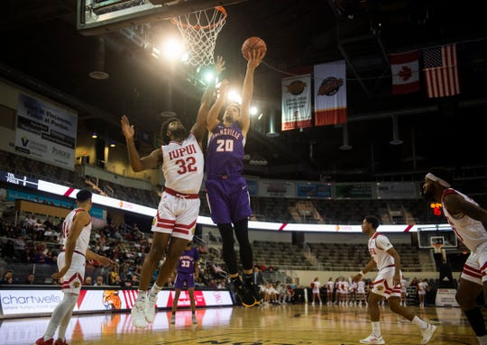 Despite the efforts of Elyjah Goss (32), Evansville's Sam Cunliffe (20) dunks on IUPUI at the Indiana Farmers Coliseum in Indianapolis, Ind., Saturday, Nov. 30, 2019.
