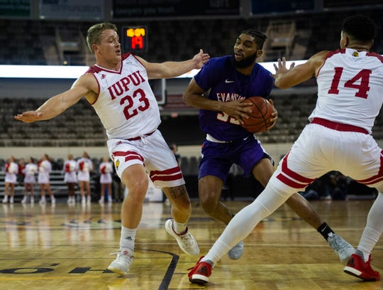 Evansville's K.J. Riley (33) moves through  IUPUI's Grant Weatherford (23) and Marcus Burk (14) at the Indiana Farmers Coliseum in Indianapolis, Ind., Saturday, Nov. 30, 2019.