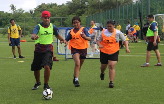 Trevor Joshua, left, Georgina Sapanza, and Megan Lava take part in a small-sided game during the Guam Football Association Special Olympics Guam Unified Soccer Jamboree Saturday.