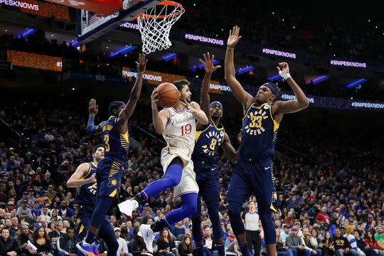 Philadelphia 76ers' Raul Neto (19) passes the ball as Indiana Pacers' Aaron Holiday (3), Justin Holiday (8) and Myles Turner (33) defend during the second half of an NBA basketball game Saturday, Nov. 30, 2019, in Philadelphia.