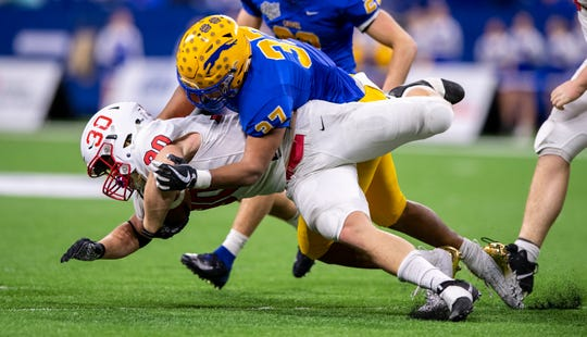 Center Grove High School junior Carson Steele (30) is hit by Carmel High School senior Ty Wise (37) during the first half of action in the 47th annual IHSAA class 6A football state finals at Lucas Oil Stadium, Saturday, Nov. 30, 2019.