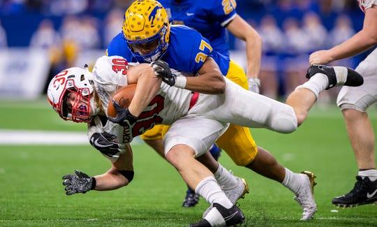 Carmel High School senior Ty Wise (37)  makes a tackle against Center Grove