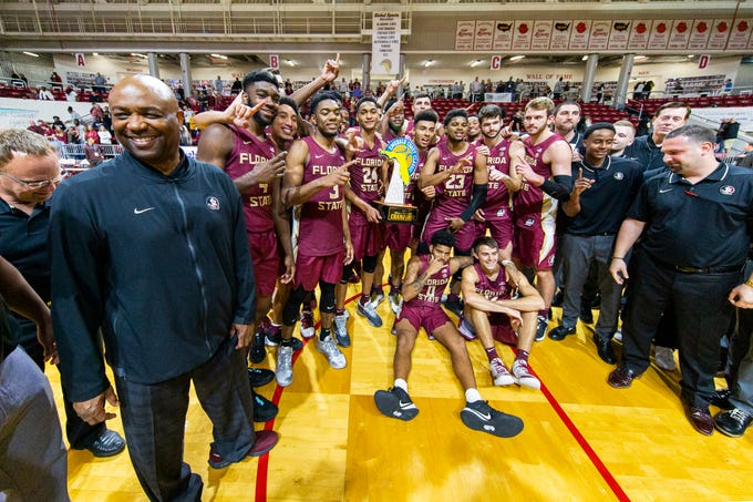 Florida State head coach Leonard Hamilton, left, smiles as players pose with the trophy after defeating Purdue 63-60 in overtime in an NCAA college basketball game at the Emerald Coast Classic in Niceville, Fla., Saturday, Nov. 30, 2019. (AP Photo/Mark Wallheiser)