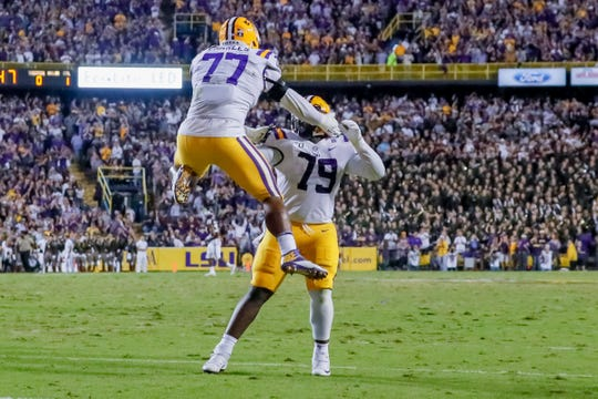 Nov 30, 2019; Baton Rouge, LA, USA; LSU Tigers offensive tackle Saahdiq Charles (77) and center Lloyd Cushenberry III (79) celebrate after a touchdown against the Texas A&M Aggies during the first quarter at Tiger Stadium. Mandatory Credit: Stephen Lew-USA TODAY Sports