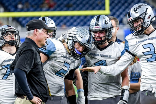 From left, Lansing Catholic's head coach Jim Ahern, Zach Gillespie, Sam Edwards and Vince Salquist celebrate their 31-17 victory over Almont's to win the3 Division 5 state football championship on Saturday, Nov. 30, 2019, at Ford Field in Detroit.