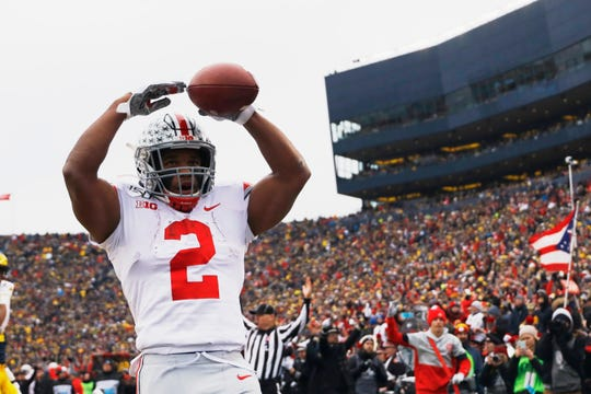 Ohio State tailback J.K. Dobbins celebrates after scoring one of his four touchdowns in Saturday's 56-27 win over Michigan.