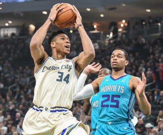 Bucks forward Giannis Antetokounmpo drives to the basket past Charlotte's PJ Washington.