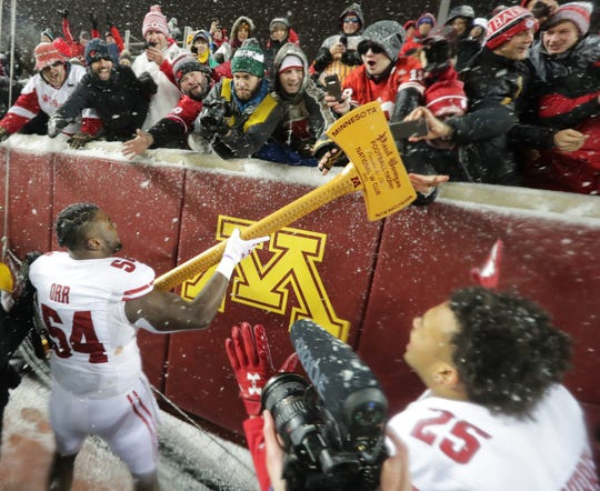 Wisconsin linebacker Chris Orr lets fans touch the Paul Bunyan Axe after Wisconsin's victory over Minnesota.