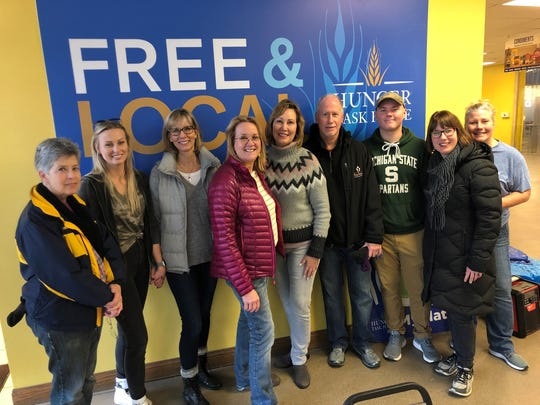 Hunger Task Force Executive Director Sherrie Tussler, fourth from the left, poses for a photo with Jaimee Niles, center, and family after they helped deliver turkeys across Milwaukee ahead of Thanksgiving.