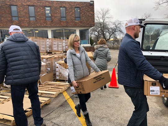 Members of Tracey Schmidt's family help load boxes of turkeys into a van, which the Hunger Task Force delivered to families in need around Milwaukee. The family raised enough money to donate 2,400 turkeys to the cause.