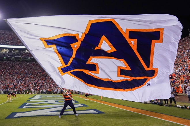 An Auburn cheerleader waves the flag after a touchdown against Alabama in the Iron Bowl on Nov. 30, 2019.