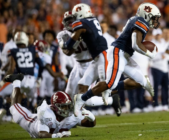 Auburn running back Shaun Shivers (8) is tripped up by Alabama linebacker Jaylen Moody (42) on a kick return in second half action in the Iron Bowl at Jordan-Hare Stadium in Auburn, Ala., on Saturday, November 30, 2019.