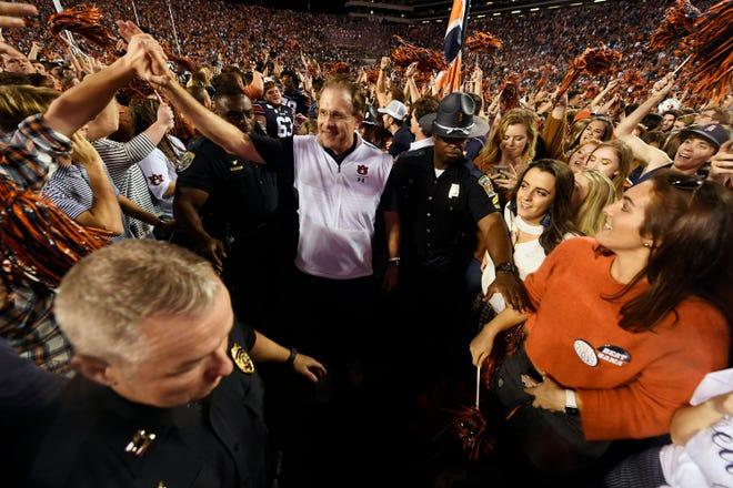 Auburn coach Gus Malzahn celebrates as fans storm the field after the Iron Bowl on Saturday, Nov. 30, 2019 in Auburn, Ala.