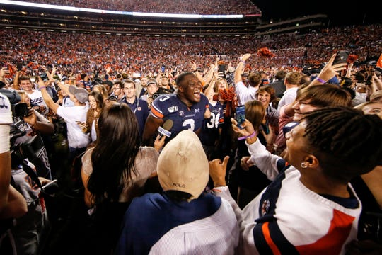 Auburn defensive end Marlon Davidson (3) reacts with fans on the field after Iron Bowl on Nov. 30, 2019.