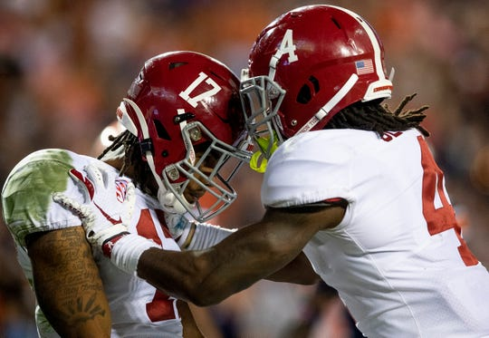 Alabama wide receivers Jaylen Waddle (17) and Jerry Jeudy (4) celebrate a Waddle touchdown catch against Auburn in second half action in the Iron Bowl at Jordan-Hare Stadium in Auburn, Ala., on Saturday, November 30, 2019.